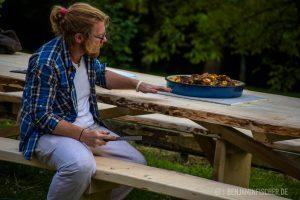 Mitarbeiter Kevin gibt dem neuen Tisch den Feinschliff, obgleich schon das Abendessen darauf steht.